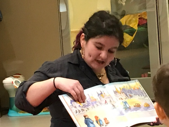 Mickey reading a story to a group of children, youth, and famlies